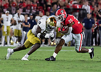 ATHENS, GA - SEPTEMBER 21: Brian Herrien #35 of the Georgia Bulldogs runs the ball as Jeremiah Owusu-Koramoah #6 of the Notre Dame Fighting Irish comes in for a tackle during a game between Notre Dame Fighting Irish and University of Georgia Bulldogs at Sanford Stadium on September 21, 2019 in Athens, Georgia.