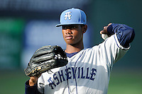 Left fielder Raimel Tapia (15) of the Asheville Tourists warms up before in a game against the Greenville Drive on Tuesday, July 1, 2014, at Fluor Field at the West End in Greenville, South Carolina. Tapia is the No. 10 prospect of the Colorado Rockies, according to Baseball America. Asheville won, 5-2. (Tom Priddy/Four Seam Images)
