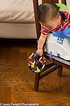 9 month old baby in infant seat strapped to chair leaning over to drop toy or to look at dropped toy