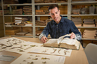 Alaska Center for Conservation Science lead botanist Justin Fulkerson consults a well-worn guide as he reviews specimens in the collection of Alaska plants in UAA's Herbarium in Beatrice McDonald Hall.