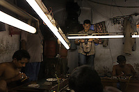 Artisanal gold smiths in Kolkata (Calcutta)....These guys make about 3-400 USD a month at the top end.  They live in the workplace... the clothes you see hanging above them are their clothes, their closet as it were.  At night they move the worktables aside and sleep on the floor and there are a few other places for them to crowd.