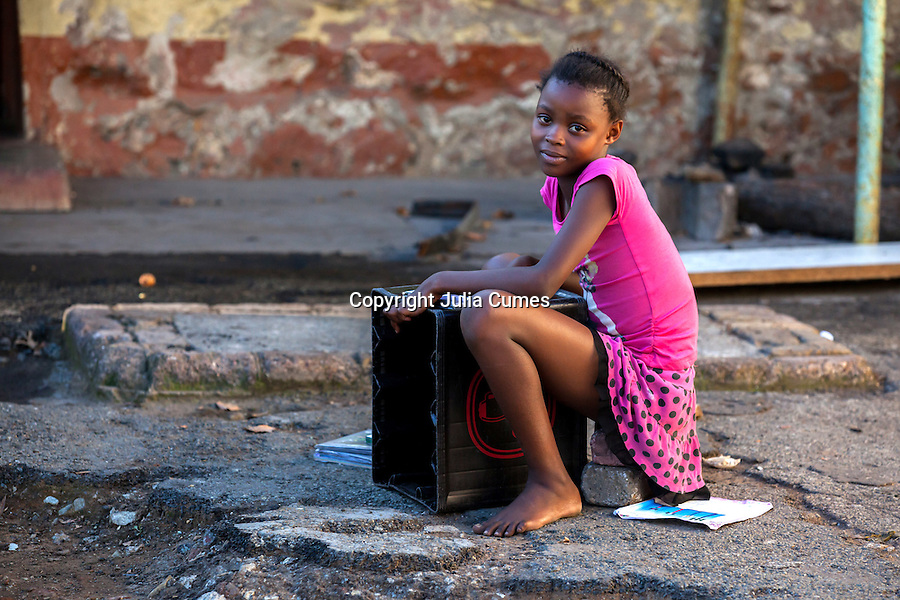 A school girl sits on stones and uses a plastic container as a desk to do her homework on at an old gold mining hostel on the outskirts of Johannesburg, South Africa.