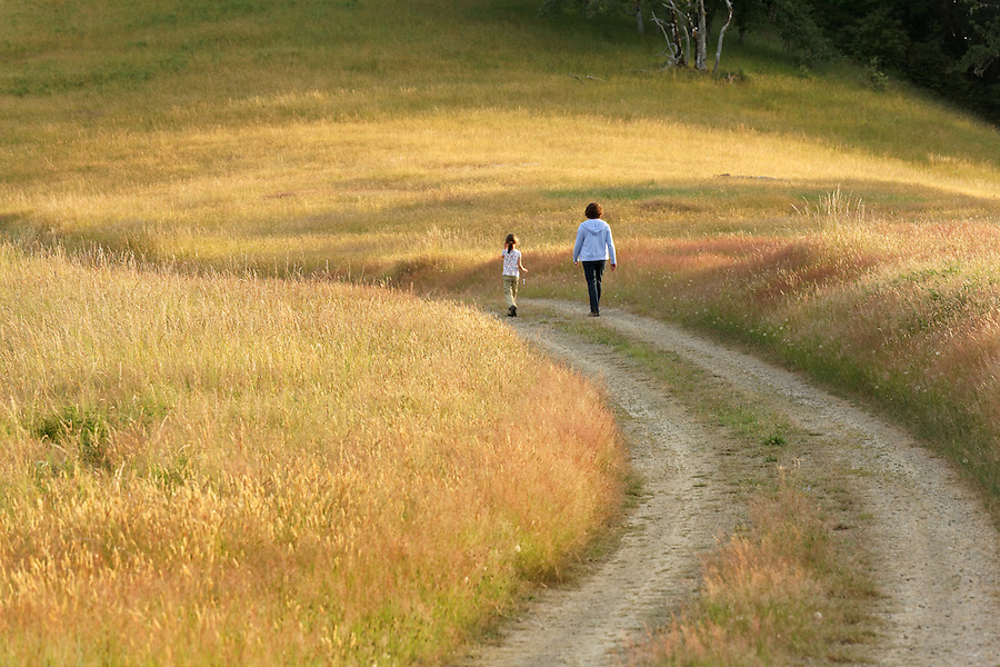 Mother and child walking on dirt road, Bald Hills prairie, Redwood National Park, California