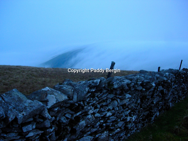 Hurrying off the hill before dark as the cloud inversion pours over the hills.<br /> <br /> Stock Photo by Paddy Bergin