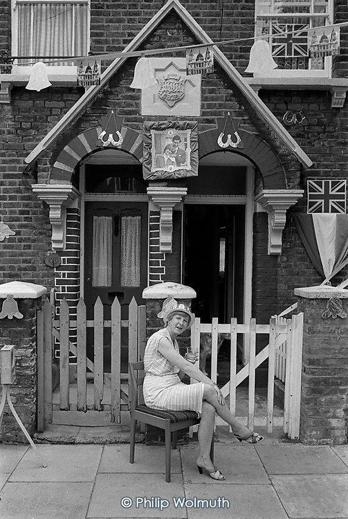 Resident outside her home during a Queens Park Estate street party to celebrate the wedding of Prince Charles and Lady Diana Spencer.  North Paddington, London 1981.