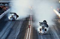 Feb. 22, 2013; Chandler, AZ, USA; NHRA top fuel dragster driver Brandon Bernstein (right) blows up alongside Mike Strasburg during qualifying for the Arizona Nationals at Firebird International Raceway. Mandatory Credit: Mark J. Rebilas-