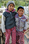 Two Guatemalan boys in traditional clothes pose outside their house in a village near Totos Santos Cuchumatan, Western Highlands, Guatemala