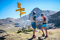Two runners checking the trail sign to their phone navigation while running the Via Valais, a multi-day trail running tour connecting Verbier with Zermatt, Switzerland.