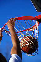 The hands of a male basketball player linger on the rim of a hoop after he dunked the ball. dunk, man, men, sports, ball, net, graphic, abstract, color contrast.