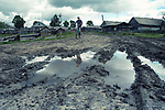 Child ride a bicycle along a village. Some Kenozero villages look neglected and abandoned nowdays
