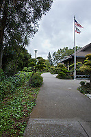 Near the entrance to the Japanese Gardens, the US and California flags fly outside the Senior Center in Hayward, California.