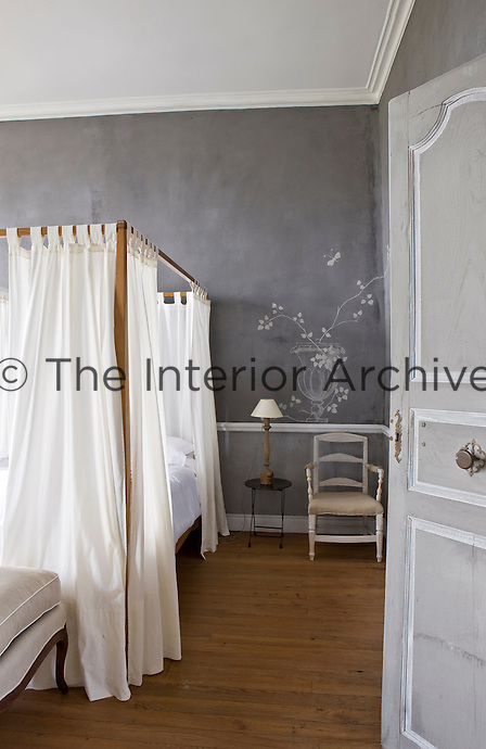 White cotton curtains surround this simple four-poster bed and the grey-painted walls have been engraved with a vase of flowers by Arnaud Lassus