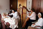"""Four days before her death, Sister M. Vivian Murphy, far left, is surrounded by her fellow Springfield Dominicans and harpist Jan Mulrooney-Kuhn in her room at the Regina Coeli infirmary at the sisters' motherhouse in Springfield, Ill. Sister Pauletta Overbeck tells her, """"Can you just put your head back and relax? I love you so much. You know that, don't you?"""" The sisters believe in accompanying each other during death, and they sign up for round-the-clock shifts so that no sister will die alone."""