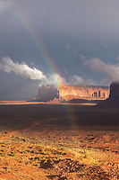 Storm light and rainbows over red rock buttes in Monument Valley, Utah.
