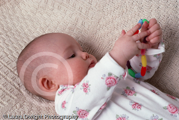 4 month old baby girl closeup on back holding and inspecting toy beads Caucasian horizontal