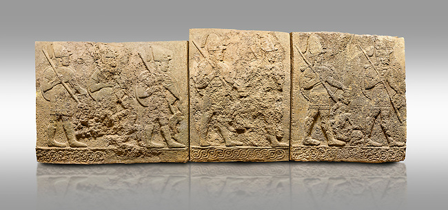 Picture & image of Hittite sculpted orthostats panels of Long Wall Limestone, Karkamıs, (Kargamıs), Carchemish (Karkemish), 900-700 B.C. Soldiers. Anatolian Civilisations Museum, Ankara, Turkey<br /> <br /> Figures of helmeted warriors. They have their shield in their back and their spear in their hand. The prisoner in their front is depicted as small. The lower part of the orthostat is decorated with braiding motifs. <br /> <br /> On a gray background.