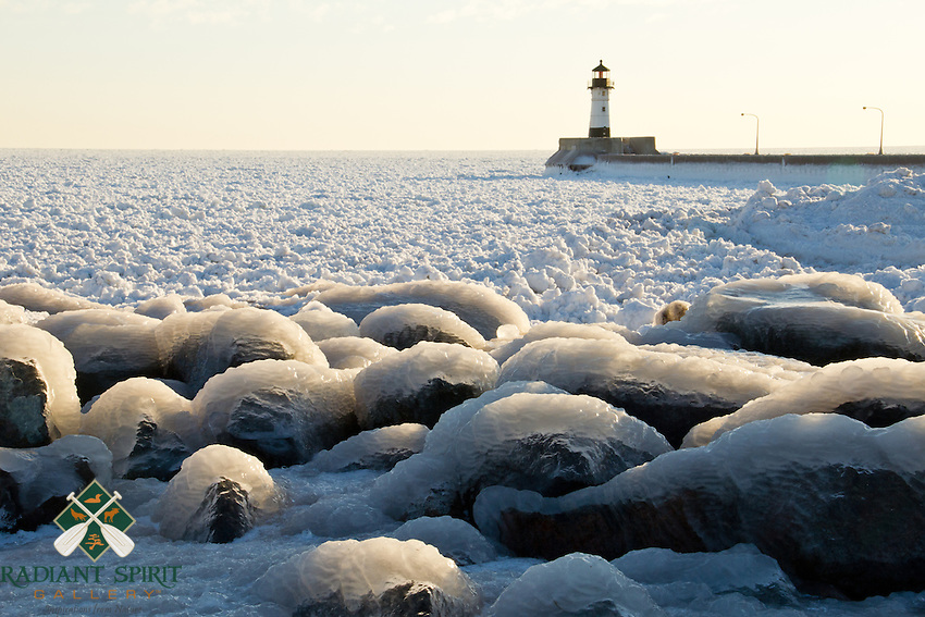 """""""Got Ice?""""<br /> <br /> Canal Park's lighthouse on Lake Superior stands amidst a field of ice and snow chunks in February. A low pressure system over Lake Superior provided wind and wave power to coat the shoreline and Lakewalk with inches-thick ice and pushed the icy chunks to the shore."""