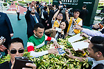 Brazilian jockey Joao Moreira (C) who rode Neorealism sign autographs while poses for photos after winning the Audemars Piguet QEII Cup horse race at Sha Tin race course in Hong Kong, China. (Photo by Marcio Rodrigo Machado / Power Sport Images)