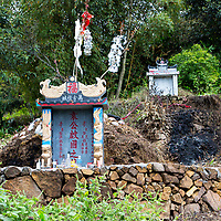 Matang, a Gejia Village in Guizhou, China.  Grave Markers in Village Cemetery, Offerings in Foreground.