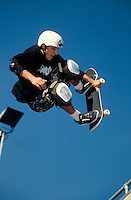 A skateboarder goes for a trick on a vert ramp.