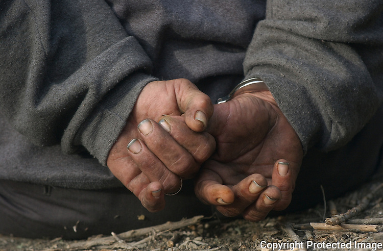 A homeless man who was arrested for illegal camping sits handcuffed in Vista, California in December, 2005.  for the North County Times
