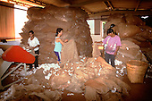 Rolandia, Parana State, Brazil. Female workers emptying sacks of raw cotton (Gossypium sp). into a machine.