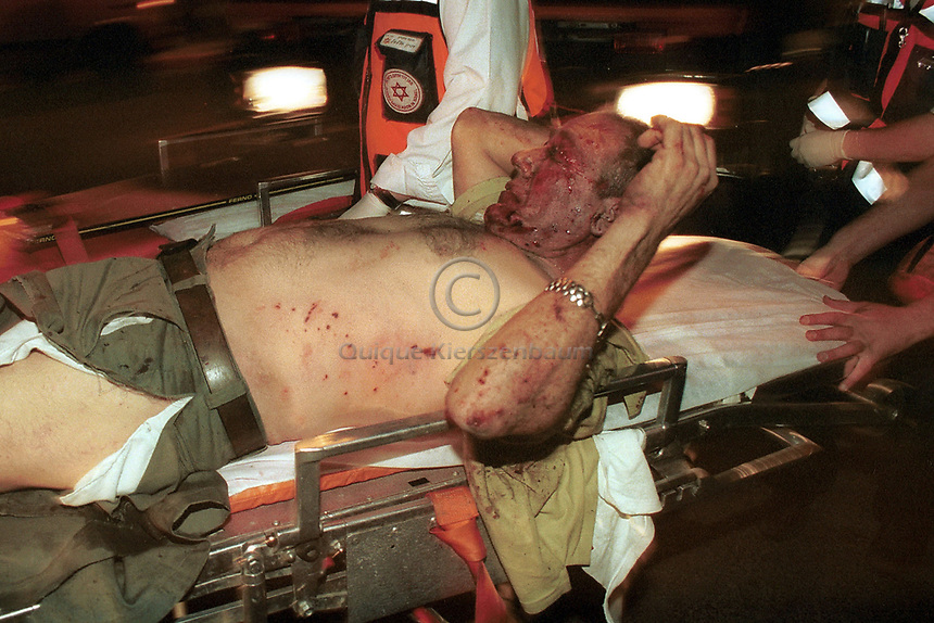 Un herido es retirado por paramedicos momentos despues de que un suicida palestino explotara en el cafe centrico Moment, a pocos metros de la casa oficial del Primer Ministro  Ariel Sharon, 11 personas murieron y decenas fueron heridos. Quique Kierszenabum