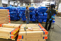 Getting ready for Iditarod 2016, long-time Iditarod volunteer Jennifer Ambrose is interviewed next to bags of straw and bundles of trail marking lathe by news station KTUU during the annual straw drop day on Tursday, February 11, 2016  at Airland Transport in Anchorage. Nearly 1700 bales of straw and thousands of wooden trail markers will be sent out to over 20 checkpoints along the trail. Iditarod 2016