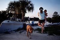 Russ Colson prepares to go fishing for the night on the Gulf of Mexico. His wife, child and the dog see him off.