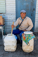 Mongolia, Bayan-Ulgii, Ulgii, Altai Mountains. Man selling fermented mares milk local market.