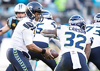 CHARLOTTE, NC - DECEMBER 15: Russell Wilson #3 of the Seattle Seahawks hands the ball off to Chris Carson #32 of the Seattle Seahawks during a game between Seattle Seahawks and Carolina Panthers at Bank of America Stadium on December 15, 2019 in Charlotte, North Carolina.