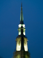 Blurred spire of building illuminated at night.