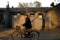A man cycles past one of the public toilets in Hou Hai, Beijing, China. About a hundred of residents have to have a toilet with the tourists. Chinese government will restore the actual face of traditional courtyards and the poor residents will subsequently be moved out of their homes..03-NOV-03