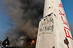 """Pres du Pont de l'Europe a Strasbourg, un membre du """"Black Block"""" passe devant l'ancien bureau des douanes, incendie durant la manifestation du 4 avril 2009 contre le sommet de l'OTAN..Credit;Hughes Leglise-Bataille/Julien Muguet/face to face"""