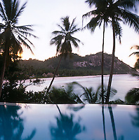 The edge of the infinity pool with the curved sandy beach of the island beyond
