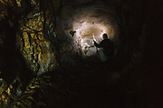 A hiker inside an old mine tunnel on Iron Mountain during the summer months in Jackson, New Hampshire USA. This tunnel is about 50 feet long.