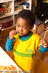 Preschool Headstart 3-5 year olds meal lunch time boy eating spagetti pasta tomato sauce vegetable broccoli vertical