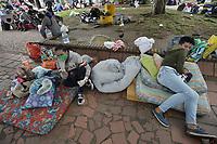 CALI - COLOMBIA, 14-04-2020: Dos mujeres aguardan a ser llamadas durante la jornada de repatriación de 215 venezolanos hacía su país desde Cali en el día 22 de la cuarentena total en el territorio colombiano causada por la pandemia  del Coronavirus, COVID-19. / Two women await to be called during the repatriation journey of 215 Venezuelans to their country from Cali during the day 22 of total quarantine in Colombian territory caused by the Coronavirus pandemic, COVID-19. Photo: VizzorImage / Gabriel Aponte / Staff