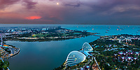 Beautiful, sunset aerial view of gardens by the bay, the city, and myriads of lit-up containerships from Marina Bay Sand rooftop, Singapore