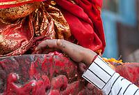 Nepal, Kathmandu.  Worshiper Touching the Platform on which Hanuman Statue Rests, Durbar Square.