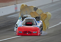 Apr. 1, 2012; Las Vegas, NV, USA: NHRA funny car driver Gary Densham crosses the track in front of John Force during the Summitracing.com Nationals at The Strip in Las Vegas. Mandatory Credit: Mark J. Rebilas-