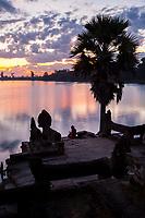 Cambodia, Srah Srang, Royal Bath at Sunset.  Visitor Checking Mobile Phone.
