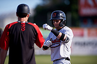 Visalia Rawhide first baseman Mark Karaviotis (24) is congratulated by first base coach Nick Evans (14) after getting a hit during a California League game against the San Jose Giants on April 13, 2019 at San Jose Municipal Stadium in San Jose, California. Visalia defeated San Jose 4-2. (Zachary Lucy/Four Seam Images)