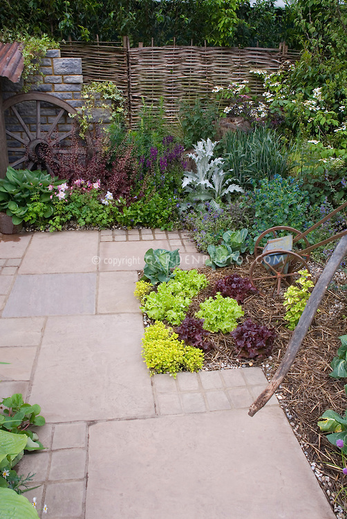 Backyard garden with vegetables and flowers, patio pavers, rustic ornaments, woven willow fence
