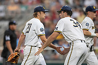 Michigan Wolverines pitcher Willie Weiss (20) is greeted after completing an inning against the Vanderbilt Commodores during Game 2 of the NCAA College World Series Finals on June 25, 2019 at TD Ameritrade Park in Omaha, Nebraska. Vanderbilt defeated Michigan 4-1. (Andrew Woolley/Four Seam Images)