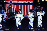 Bon dancers wearing traditional costumes mindfully move with the drum beat during the Japanese cultural Bon Dance to honor the dead.