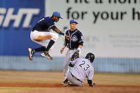 Asheville Tourists shortstop Rosell Herrera #7 leaps over a hard sliding Angel Rosario #23 during a game against the  Kannapolis Intimidators at McCormick Field on May 9, 2013 in Asheville, North Carolina. The Intimidators won the game 13-12. (Tony Farlow/Four Seam Images).