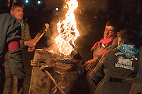"""Reveler set a bull's horns on fire during the festivity called toro de jubilo in Medinaceli, near Soria, on november 14, 2015. """"El toro de jubilo"""" is a festival that takes place in Medinaceli. Every year, on the second weekend of November,  the bull is surrounded and restrained by participants. During this festival, a bull is tied to a post. Balls are then placed on each horn of the bull and lit a flame. A think layer of mud on the back and face of the bull helps protect the bull from physical injury or burns. The bull is then released by the square, which has 5 fire lit bonfires symbolizing five martyrs.   © PEDRO ARMESTRE"""