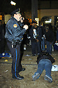 A police officer calls for help after four people were shot, one fatally, on the parade route of Muses parade on St. Charles Avenue in New Orleans, after six or seven shots rang out, at about 9 p.m., Monday, February 18, 2004..(AP PHOTO/CHERYL GERBER)...