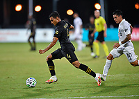 LAKE BUENA VISTA, FL - JULY 18: Eddie Segura #4 of LAFC dribbles away from Cristian Pavón #10 of LA Galaxy during a game between Los Angeles Galaxy and Los Angeles FC at ESPN Wide World of Sports on July 18, 2020 in Lake Buena Vista, Florida.
